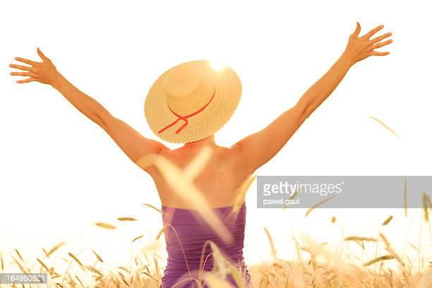 Giovane donna con le braccia spalancate contro bianco cielo
