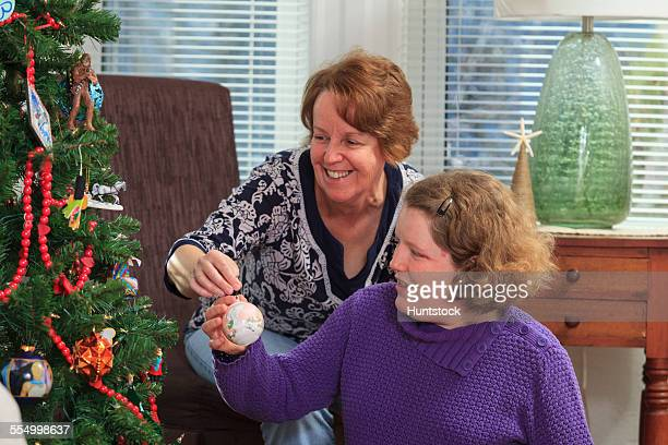 Young woman with Autism and her mother putting an ornament on Christmas tree