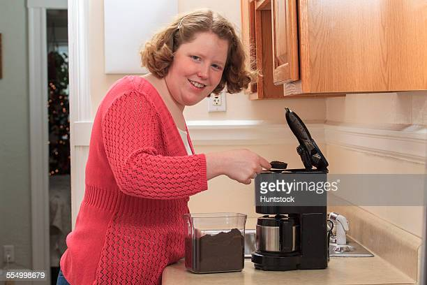 Young woman with Autism making coffee in her kitchen