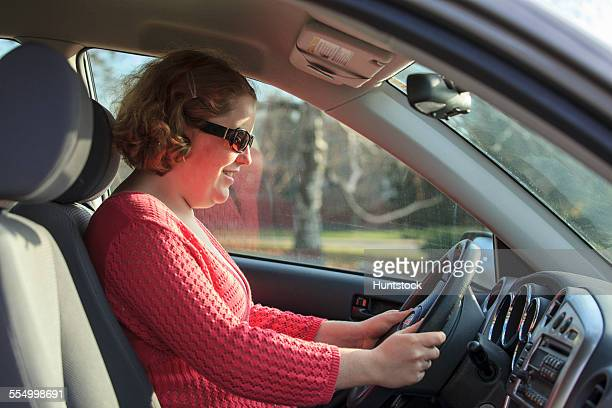 Young woman with Autism sitting in the drivers seat of her car