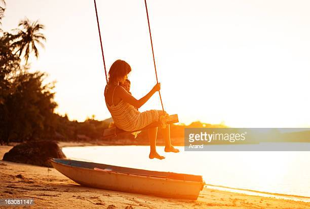 young woman with baby on beach swing