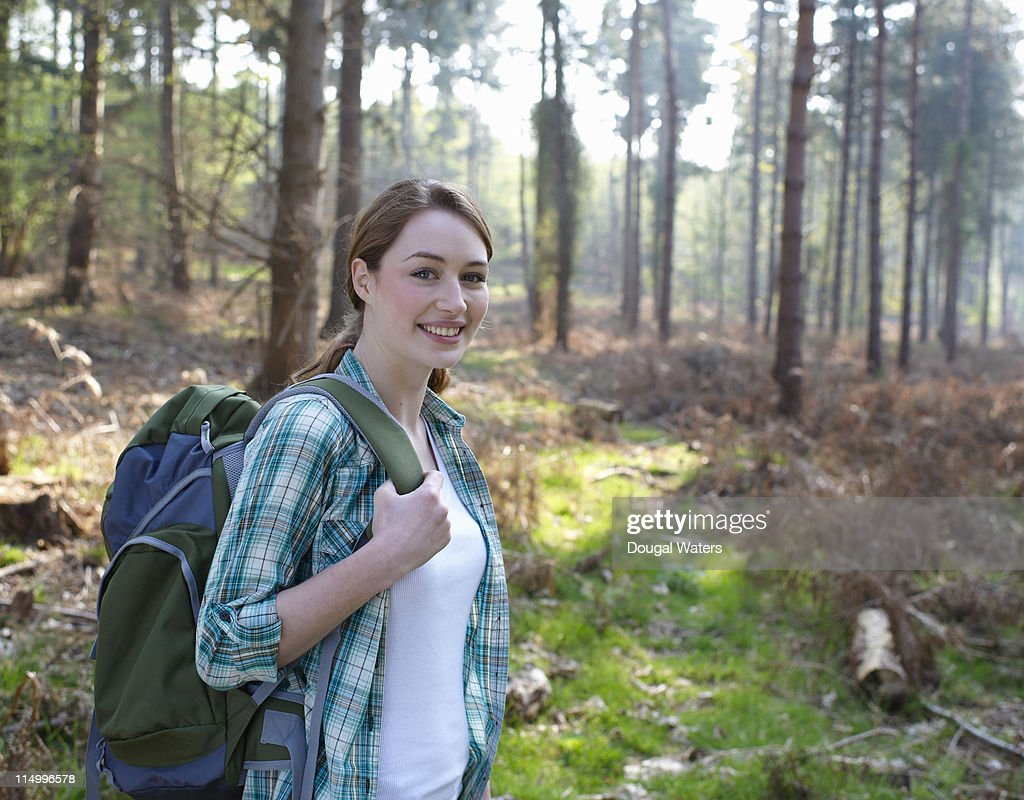 Young woman with back pack standing in woodland. : Stock Photo