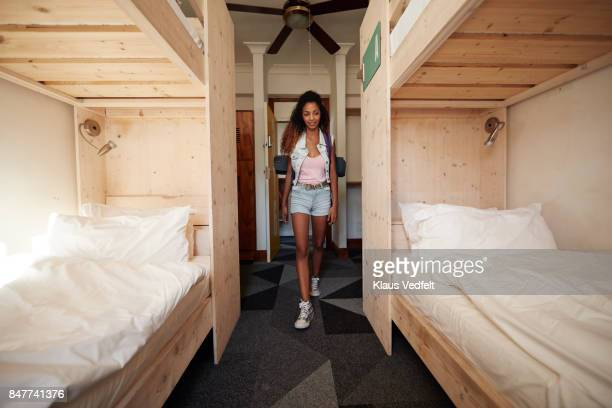 Young woman with backpack, arriving at empty hostel room
