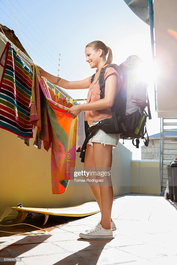 Young woman with backpack hanging laundry : Foto de stock