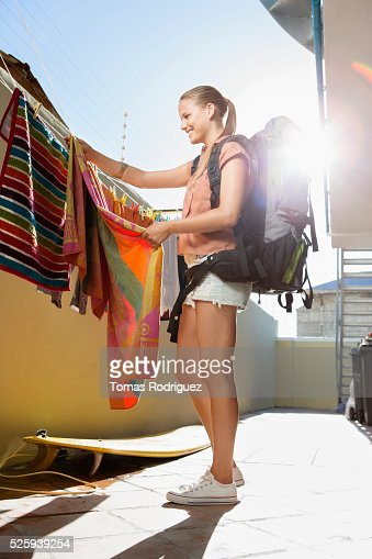 Young woman with backpack hanging laundry : Stock-Foto