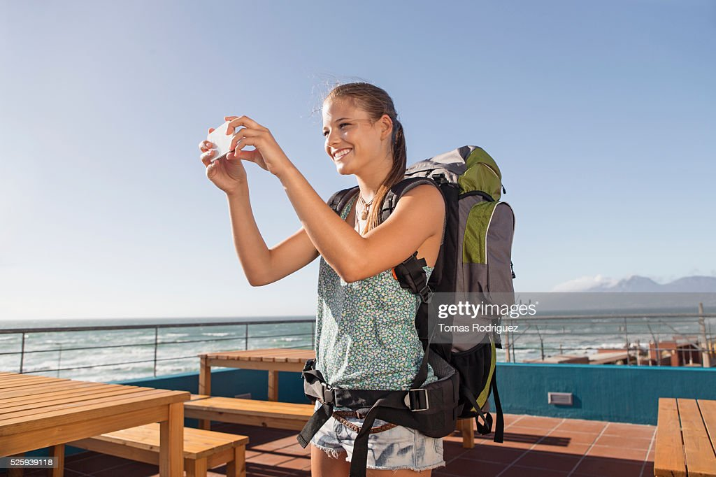Young woman with backpack taking pictures : Stock Photo