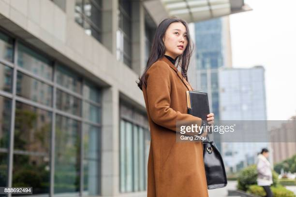 young woman with bag and notebook going out of modern building