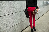 Young woman with bag and skateboard wearing red trousers, partial view