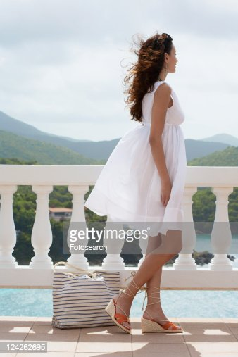 Young woman with bag standing on balcony