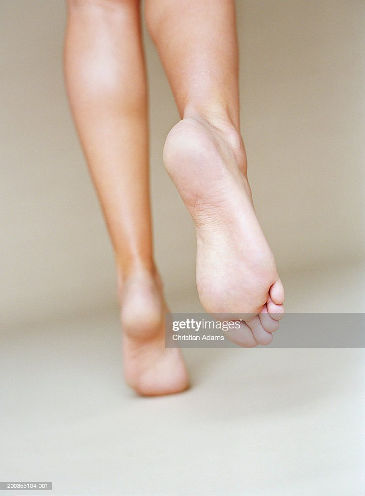 Young woman with bare feet and legs, running, rear view, close-up : Stock Photo