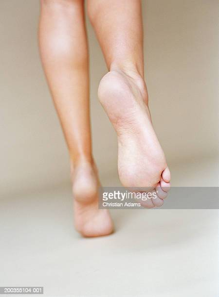 Young woman with bare feet and legs, running, rear view, close-up