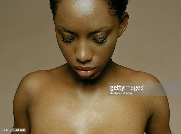 Young woman with bare shoulders looking down, close-up