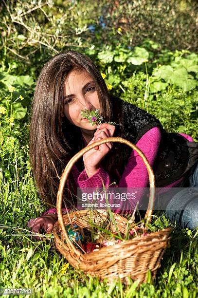 Young woman with basket picking flowers