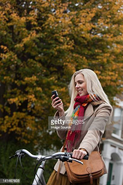 Young woman with bicycle, looking at cellphone