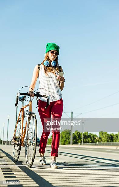 Young woman with bicycle on pavement looking at cell phone