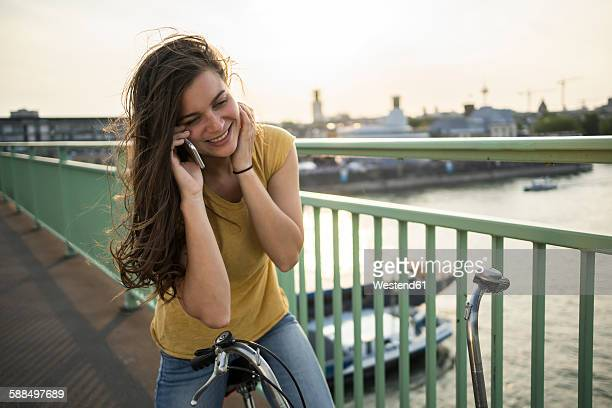 Young woman with bicycle standing on Rhine bridge telephoning with smartphone