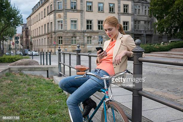 Young woman with bicycle using smart phone
