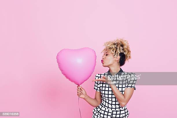 Mujer joven con grandes rosa corazón