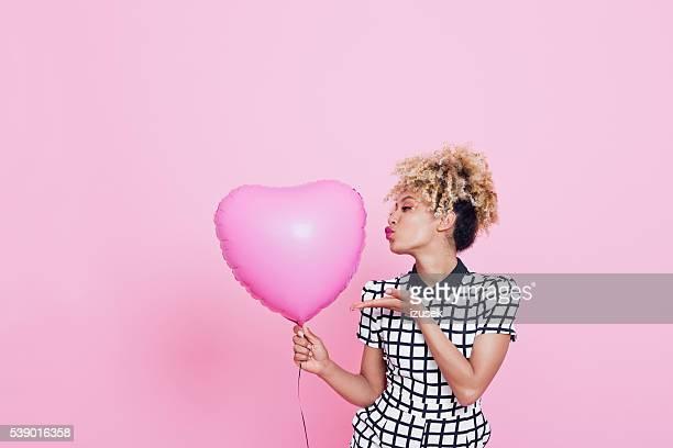 Jeune femme avec gros cœur rose