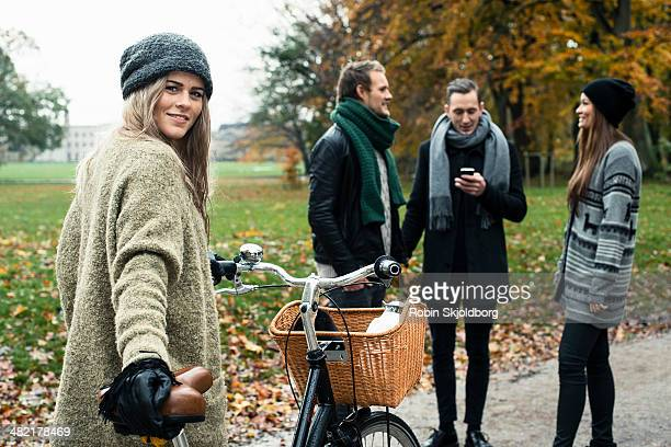 Young woman with bike, friends in background