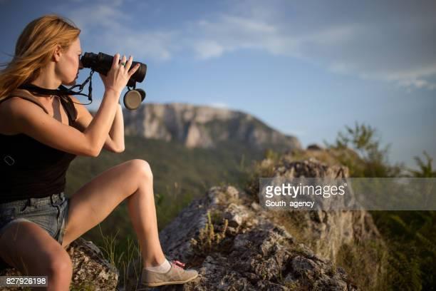 Junge Frau mit dem Fernglas auf dem Gipfel des Berges