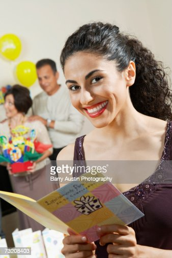 Young woman with birthday card, indoors, portrait