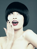Young woman with black bob gasping