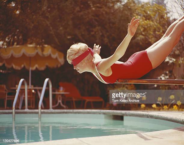 Young woman with blindfold balancing on diving board