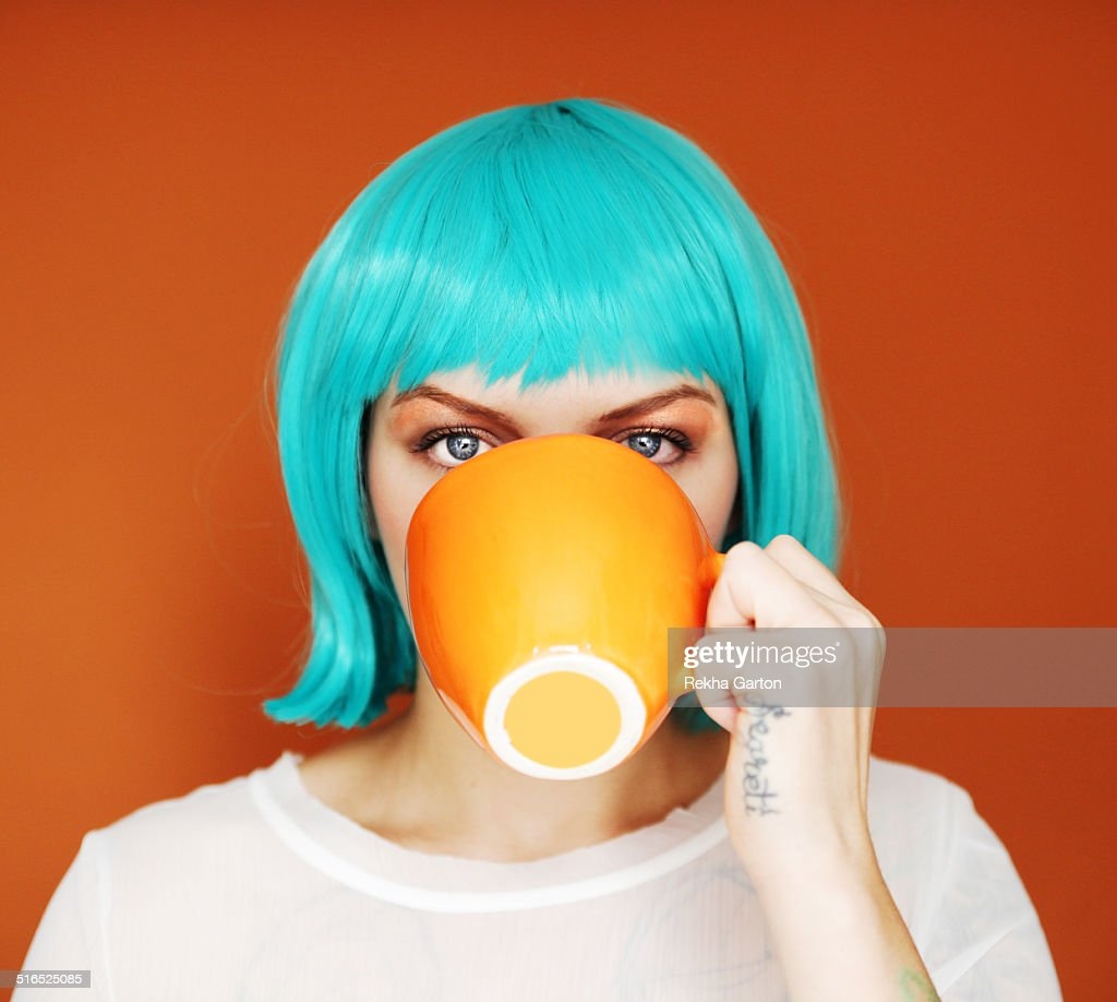 Young woman with blue hair drinking : Stock Photo