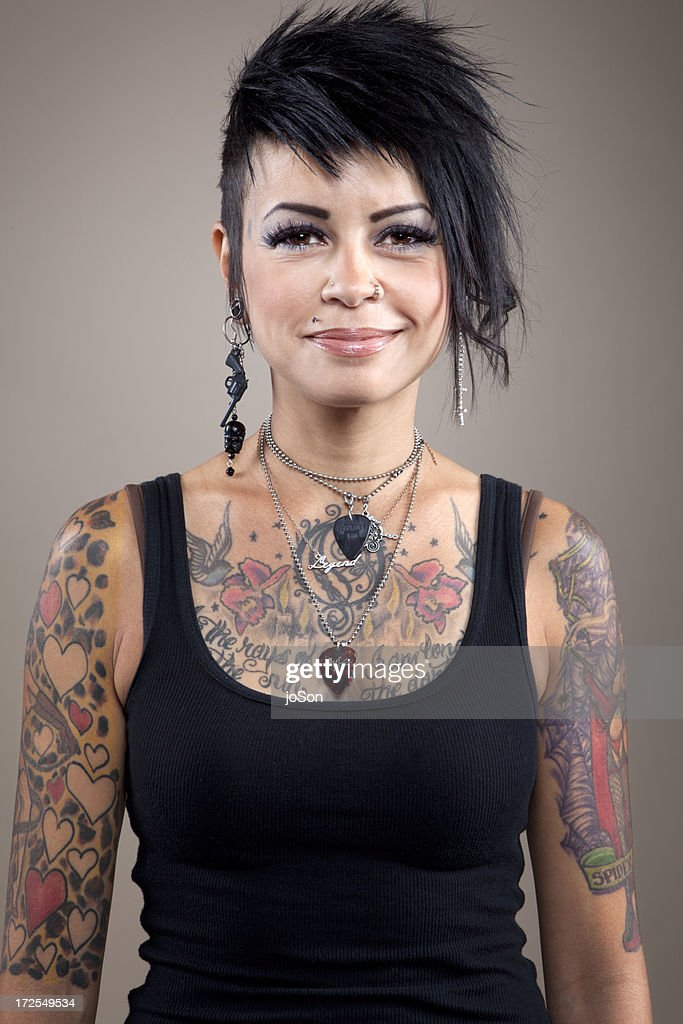 Young woman with body tattoos miling, portrait : Stock Photo