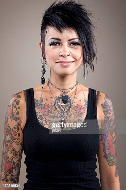 Young woman with body tattoos miling, portrait