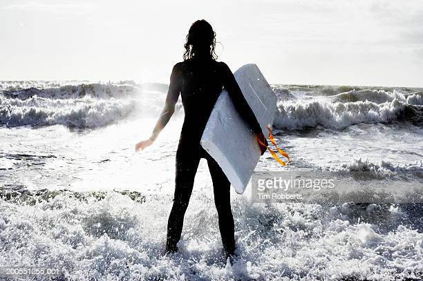 Young woman with boogie board at beach, rear view