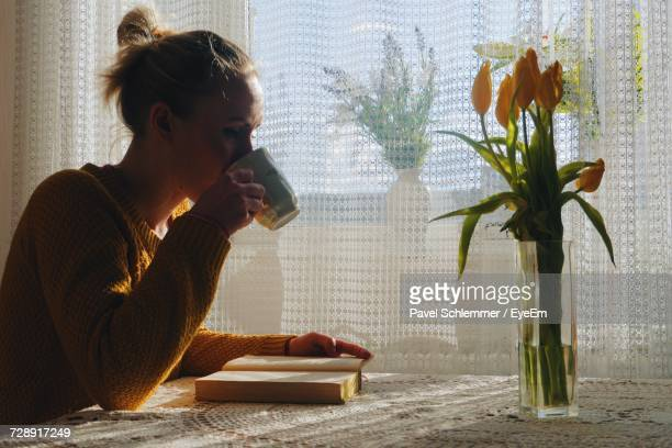 Young Woman With Book Drinking Tea While Sitting At Table In House
