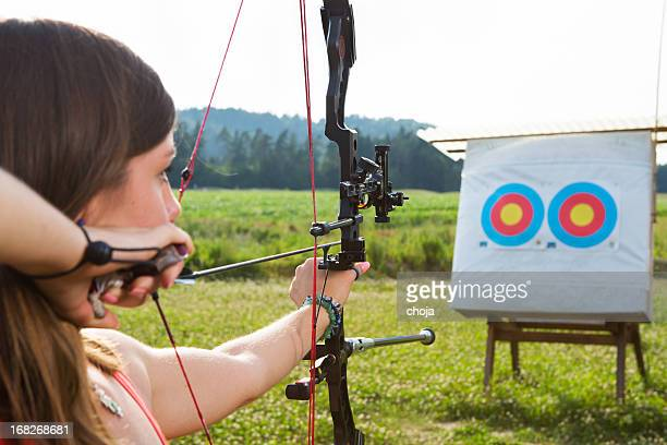 Young woman with bow and arrow practicing target shooting