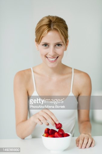 Young woman with bowl of strawberries