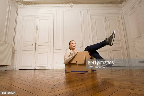 Young woman with box in a new home