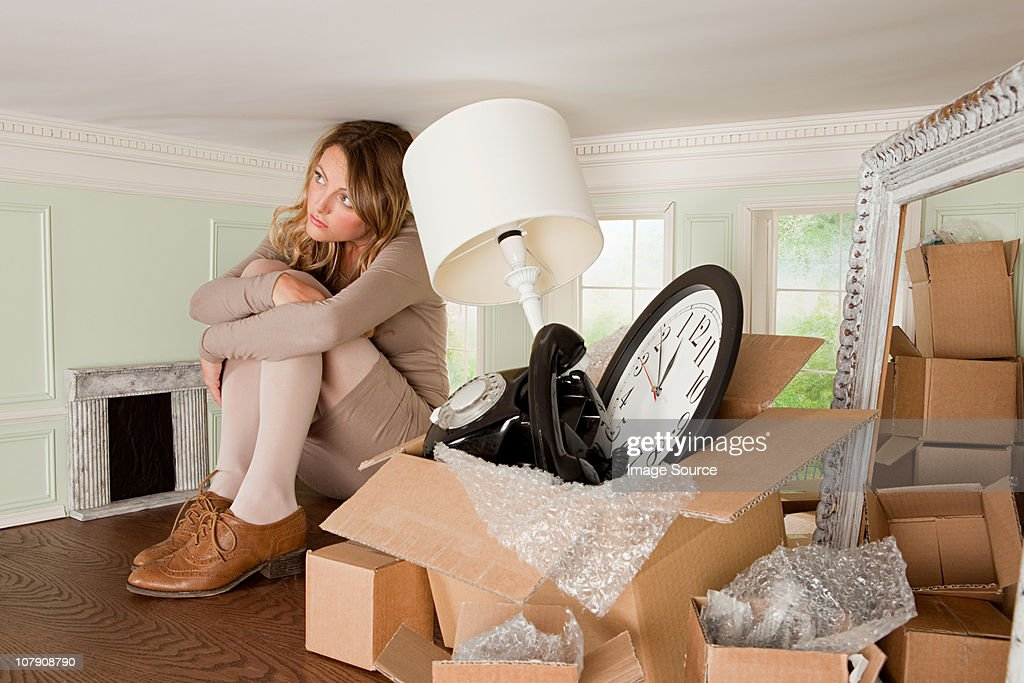 Young woman with box of objects in small room : Stock Photo
