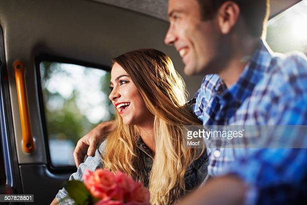Young woman with boyfriend and bunch of roses in city taxi