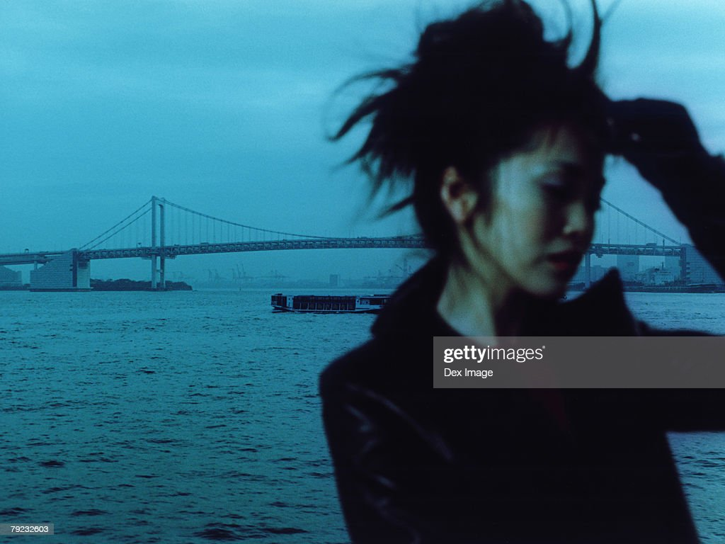 Young woman with bridge in background, portrait : Stock Photo