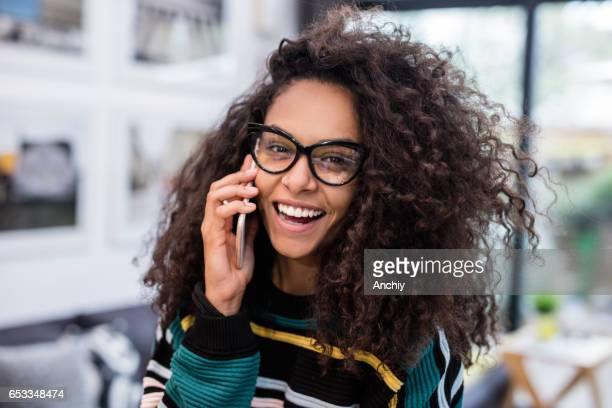 Young woman with bright smile talking on the phone