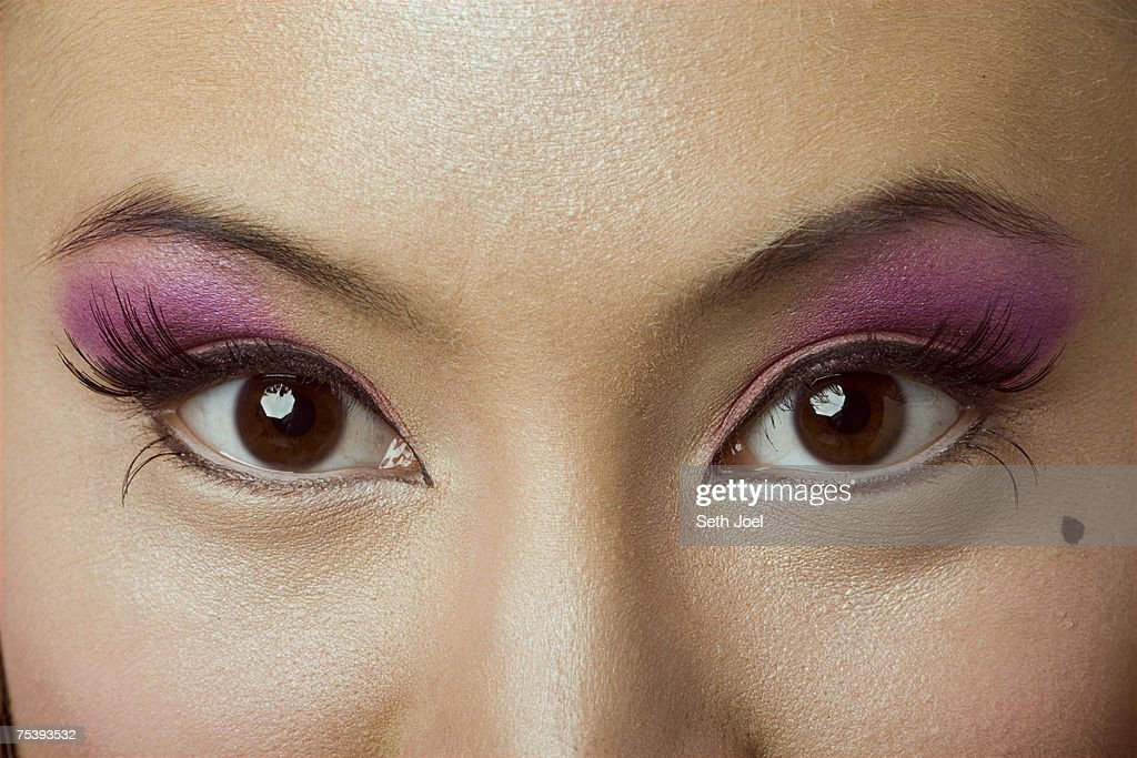 Young woman with brown eyes wearing false eyelashes and colourful make up, extreme close-up