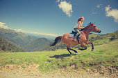 Young woman with brown horse at gallop on mountain outdoor