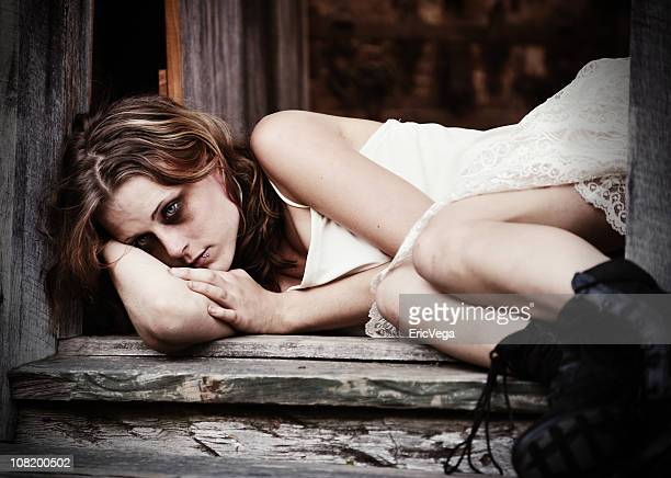 Young Woman with Bruised Black Eye Lying in Doorway