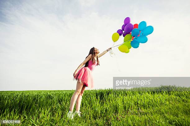 Young woman with bunch of balloons blown away by wind