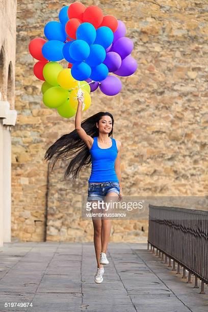 Junge Frau mit Haufen bunte Ballons springen auf Brücke