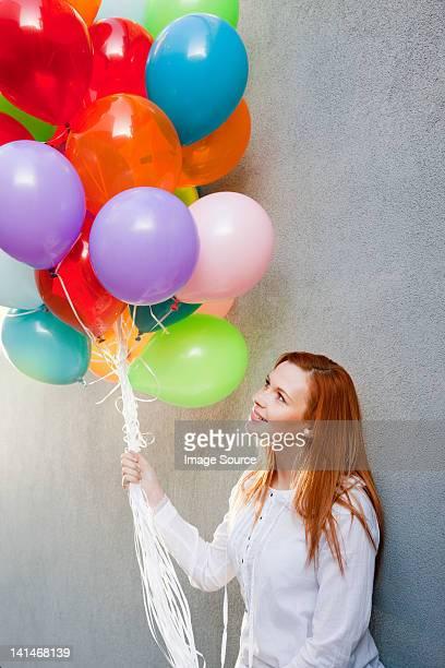 Junge Frau mit Haufen bunte Ballons