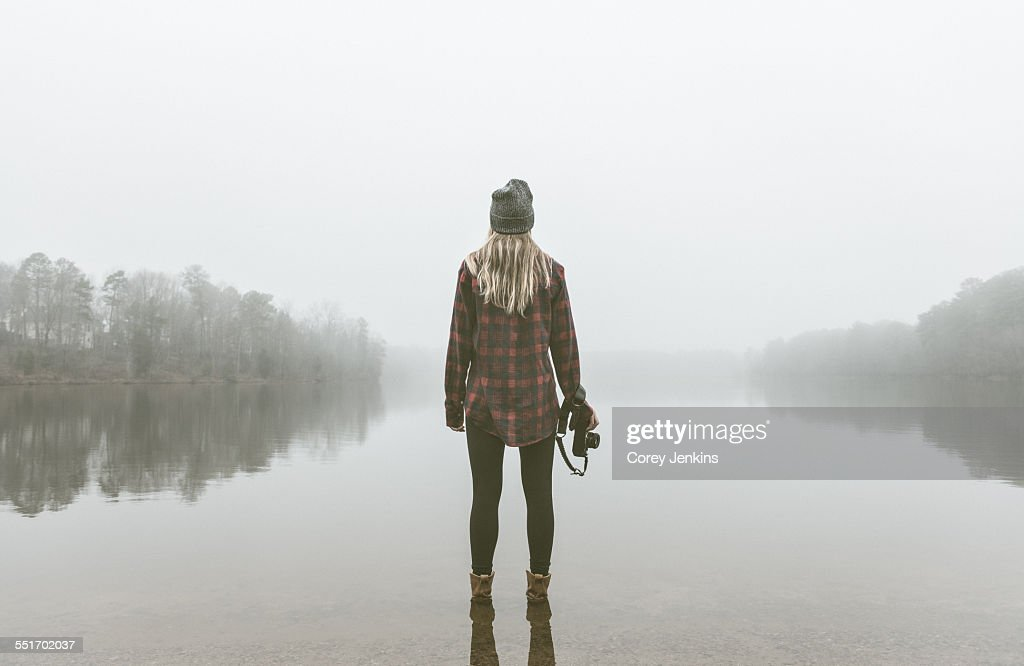 Young woman with camera standing in misty lake : Stock Photo