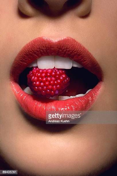 Young woman with candy between teeth, close up.
