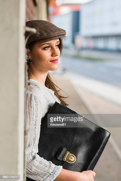 Young woman with cap and bag outdoors