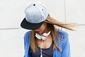 Portrait of young woman with cap and headphones looking down.